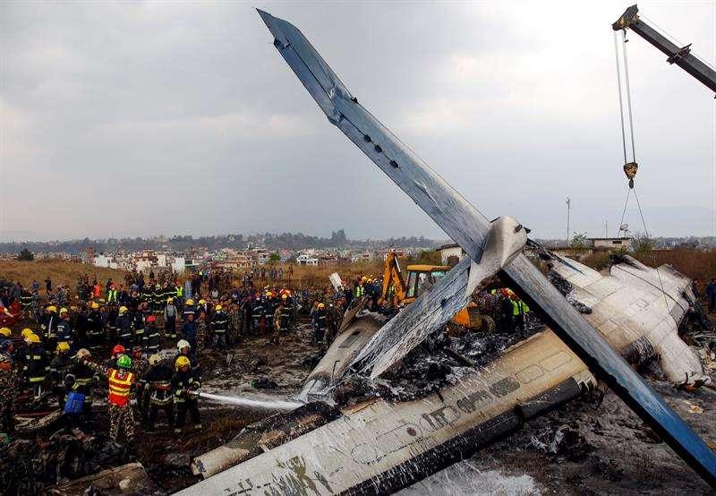 Miembros de los servicios de rescate buscan supervivientes entre los restos del avión que se estrelló en el aeropuerto de Katmandú (Nepal). EFE
