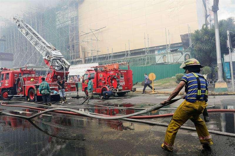 Un bombero saca una manguera durante la extinción de un incendio en un hotel y casino en Manila, Filipinas. EFe