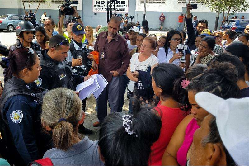 Un policía lee una lista con nombres de sobrevivientes a los familiares de los reclusos del centro de reclusión de la Policía Estadal de Carabobo (centro). EFE