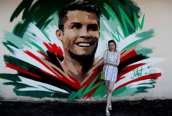 La artista rusa Julia Antipova posa frente al mural que creó de Cristiano. Foto: EFE