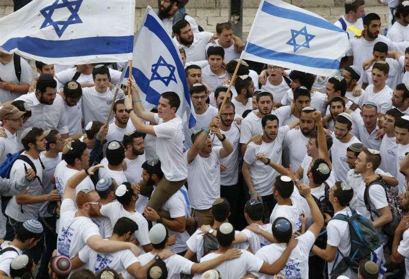 Jóvenes israelíes ondean banderas nacionales fuera de la Puerta de Damasco de la Ciudad Vieja, en Jerusalén. Foto: AP