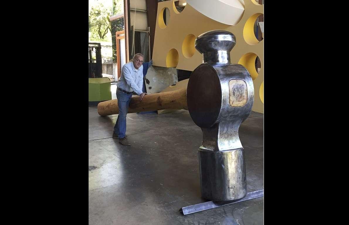 En esta foto de abril de 2017 lanzada por Doug Unkrey, el artista Unkrey posa para una foto con un gran martillo que creó en su estudio en Geyserville, California. AP