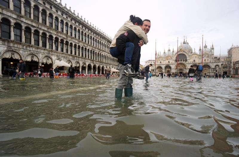 Un hombre carga a sus espaldas con su hija en la Plaza de San Marco, inundada como consecuencia del temporal de lluvia registrado en Venecia. EFE