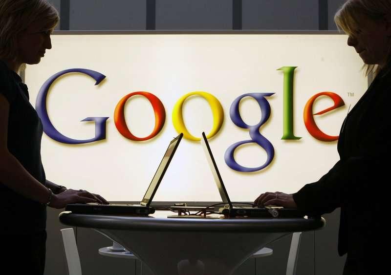 Expositores de Google trabajan frente a un letrero iluminado en la feria industrial Hannover Messe en Hannover, Alemania.  AP