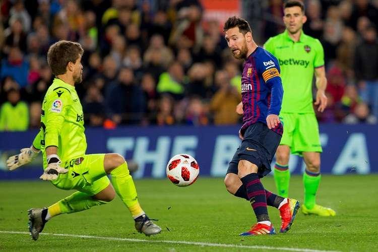 Leo Messi (centro), golpea el balón ante el guardameta del Levante, Aitor Fernández (izq.) Foto: EFE