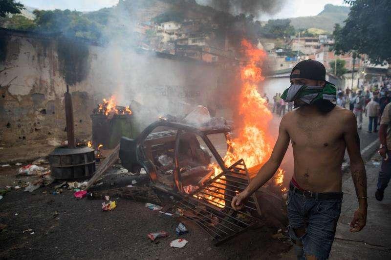 Un grupo de personas se manifiestan en una calle en las inmediaciones de un comando de la Guardia Nacional Bolivariana este lunes, en Carcas (Venezuela). EFE