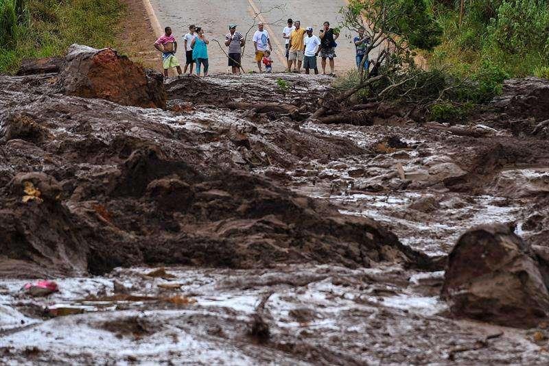 Pobladores observan este sábado el desastre causado por la rotura de una presa que contenía residuos minerales de la compañía Vale, en Brumadinho, municipio de Minas Gerais (Brasil). EFE