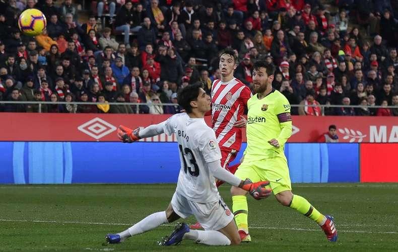 Messi toca el balón por el encima del arquero del Girona. / Foto AP