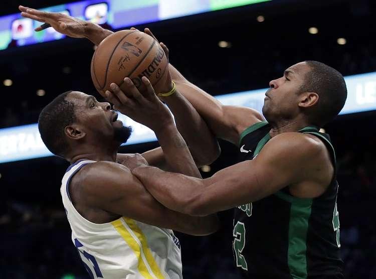 Kevin Durant (izq.) recibe una falta de  Al Horford./ Foto AP