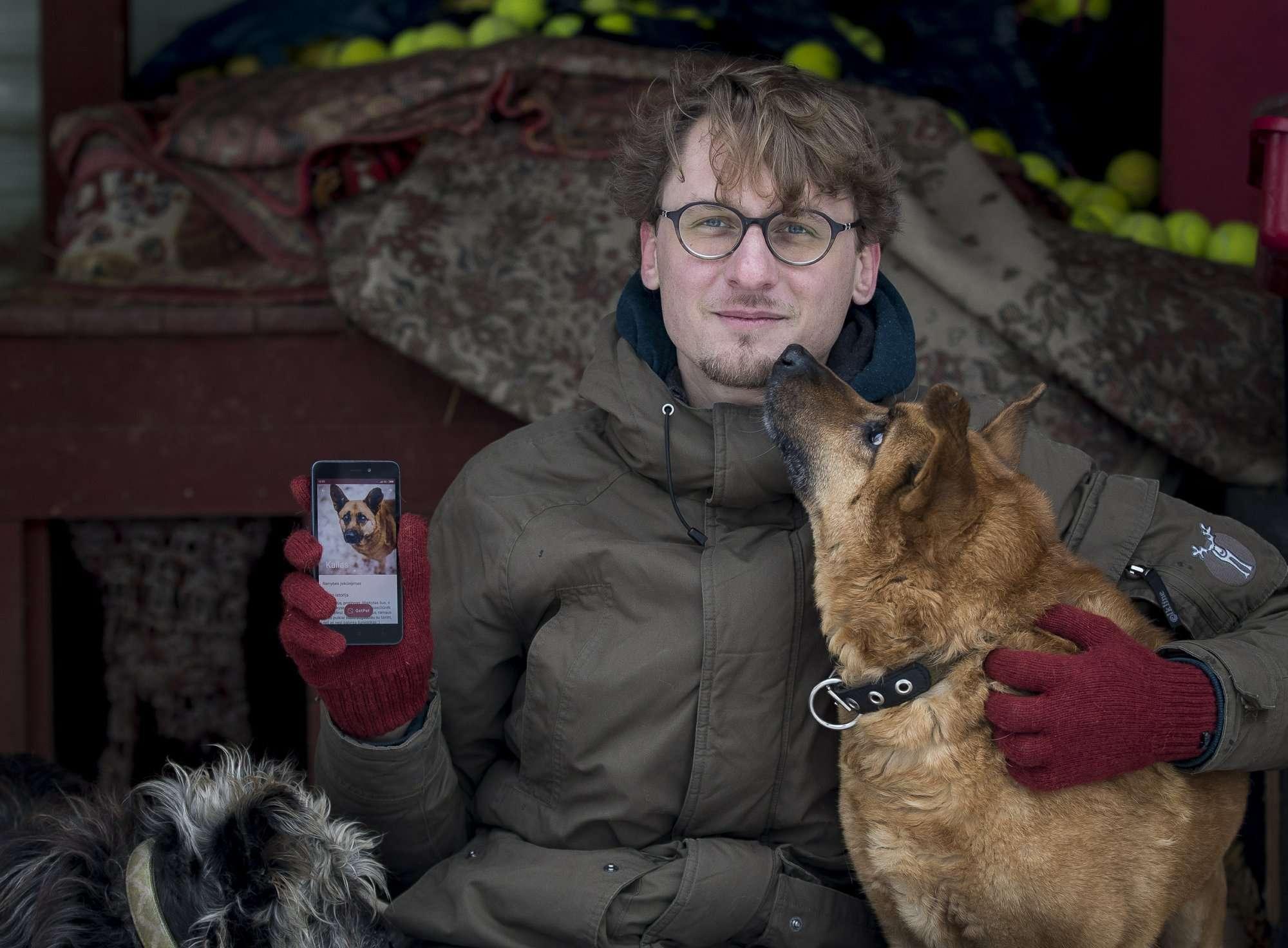 En esta foto Vaidas Gecevicius, quien desarrolló una aplicación que ayuda a hacer coincidir perros callejeros con dueños potenciales, posa para una foto con un perro y muestra el perfil de este perro en la aplicación en Vilnius, Lituania. AP