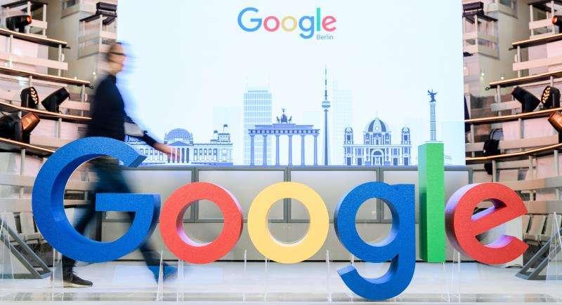 Un empleado camina junto al logotipo de la multinacional estadounidense Google. EFE/Archivo