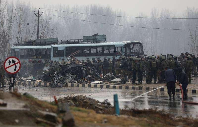 Varios policías observan el lugar en el que al menos 20 policías murieron y decenas más resultaron heridos hoy por un ataque con bomba contra el vehículo en el que viajaban en una carretera del distrito de Pulwama de la Cachemira india. EFE