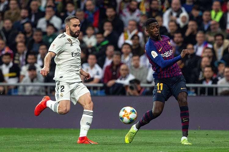 El delantero francés del FC Barcelona Ousmane Dembele (d) lucha con Dani Carvajal, del Real Madrid. Foto: EFE