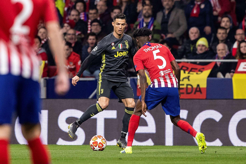 Cristiano Ronaldo (i) pelea un balón con el centrocampista ghanés del Atlético de Madrid Thomas Partey durante el partido de ida de octavos de final de la Liga de Campeones. /EFE