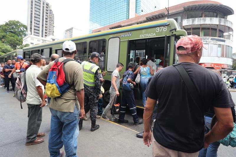Un grupo de personas toma autobuses de servicio público hoy, jueves en Caracas. Los venezolanos reanudan sus actividades luego del fallo eléctrico que hace una semana afectó casi todo el país y por el que se paralizaron los servicios durante al menos 100