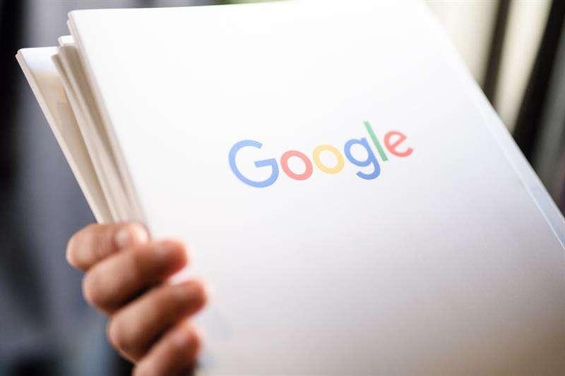 Un empleado sostiene un dosier con el logotipo de la multinacional estadounidense Google. EFEArchivo