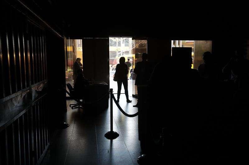 Un grupo de personas permanece en medio de la oscuridad al interior del edificio de la Asamblea Nacional este lunes en Caracas (Venezuela). EFE