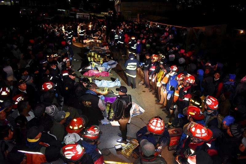 Bomberos permanecen junto a los cuerpos de las víctimas en el lugar donde se produjo un atropello por un vehículo de transporte pesado en la entrada del casco urbano del municipio de Nahualá (Guatemala). EFE