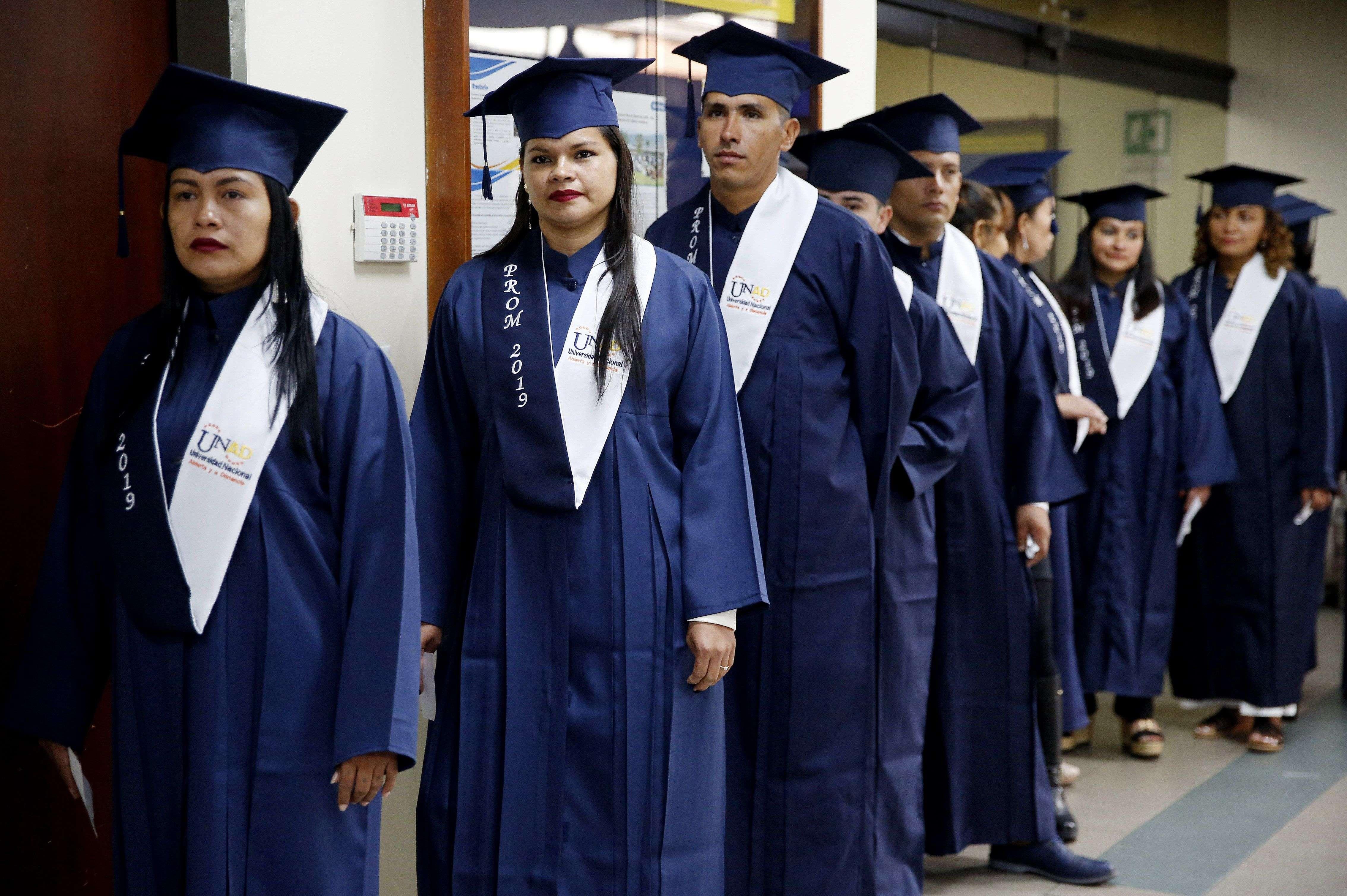 Un grupo de exguerrilleros de las FARC hacen fila para recibir su diploma de bachillerato.