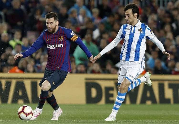 El delantero del FC Barcelona Leo Messi (i) juega un balón ante Rubén Pardo, de la Real Sociedad. Foto: EE