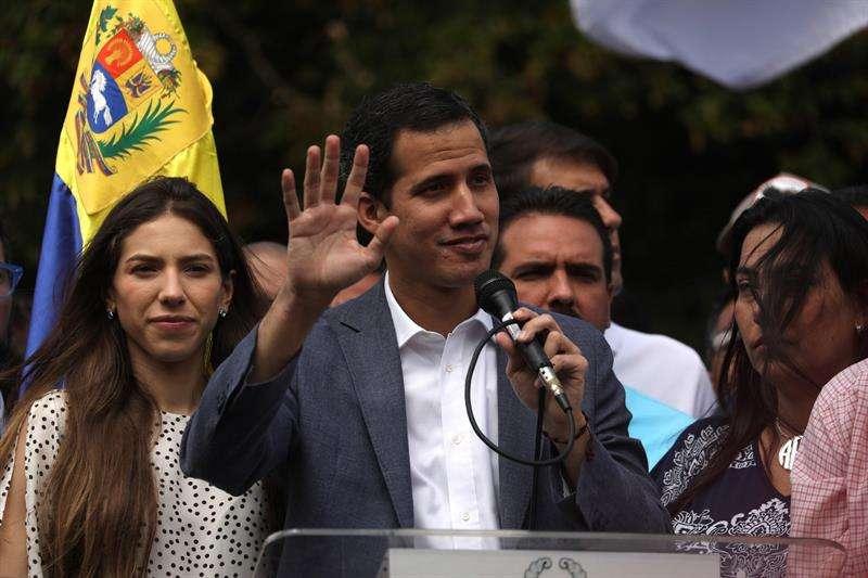 El jefe de la Asamblea Nacional de Venezuela (AN, Parlamento), Juan Guaidó (c), habla durante un cabildo abierto con cientos de sus simpatizantes y en compañía, además de otros, de Lilian Tintori (c-i), este sábado, en Caracas (Venezuela). EFE