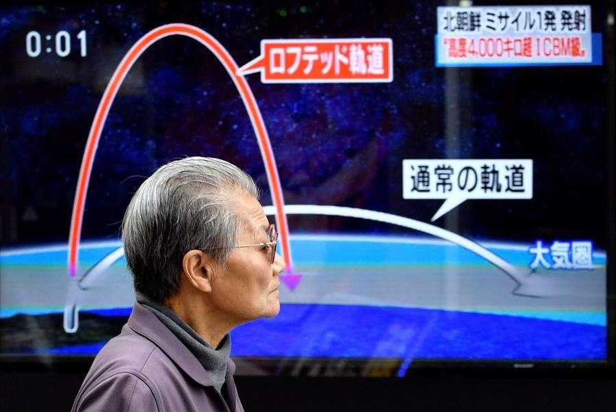 Un ciudadano camina frente a un televisor que muestra los detalles del lanzamiento de un misil balístico de Corea del Norte. EFE