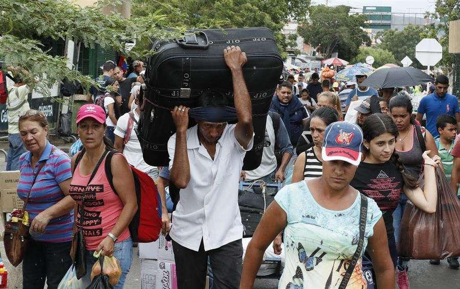 Ciudadanos venezolanos regresan con sus maletas llenas de provisiones por el puente internacional Simón Bolívar este sábado, en Cúcuta (Colombia). EFE