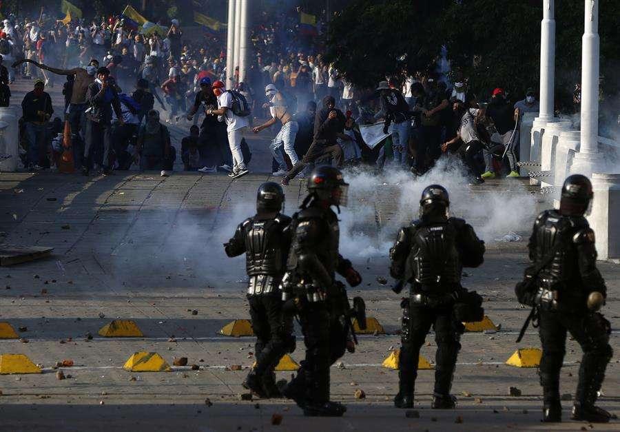 Manifestantes enfrentan a la Policía durante el desarrollo de las protestas y movilizaciones por el denominado Paro Nacional este jueves, en Cali (Colombia). EFE