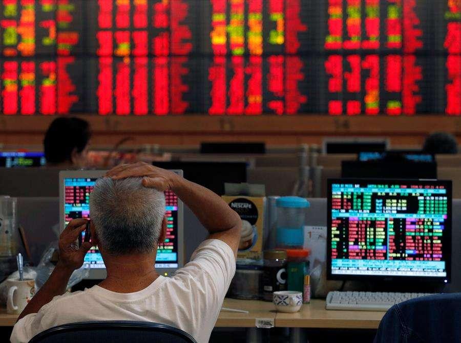Un inversor tailandés reacciona ante una pantalla llena de valores bursátiles en rojo en una empresa de corretaje bursátil en Bangkok (Tailandia) este martes. EFE