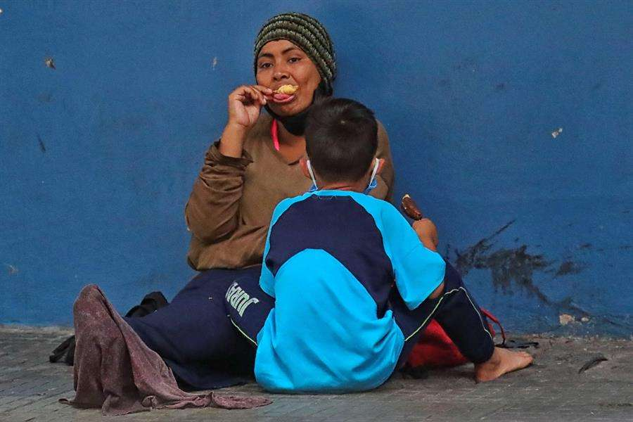 Una mujer y un niño permanecen sentados en una calle en la que piden diner este miércoles en Tegucigalpa (Honduras). EFE
