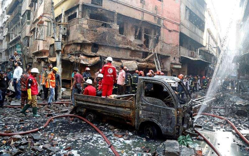 Varios bomberos inspeccionan los escombros de los edificios afectados en el incendio declarado esta madrugada en el barrio de Chawkbazar, en el casco viejo de Dacca (Bangladesh). EFE