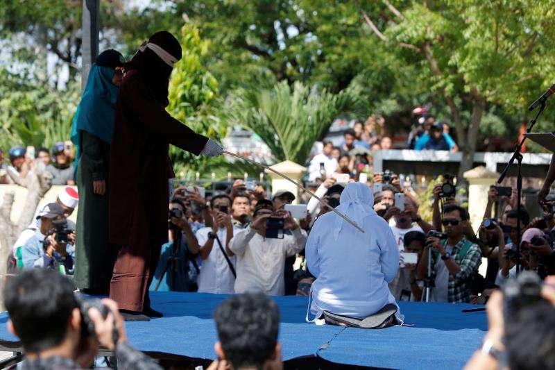 Un verdugo castiga públicamente a una mujer por vender alcohol en Banda Aceh, Indonesia, hoy, 13 de julio de 2018. EFE