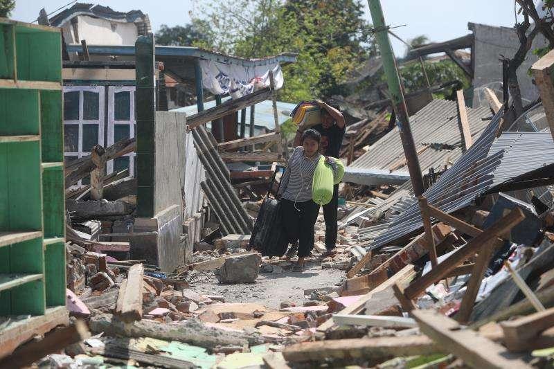 Residentes cargan con sus pertenencias entre los escombros tras los terremotos que desde el pasado domingo azotan el norte de la isla de Lombok (Indonesia). EFE