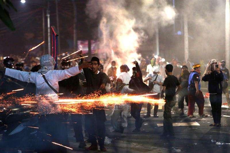 Manifestantes indonesios se enfrentan a los agentes de la policía antidisturbios durante una protesta tras el anuncio de los resultados de las elecciones presidenciales, frente al edificio de la Junta de Supervisión de Elecciones, en Yakarta. EFE