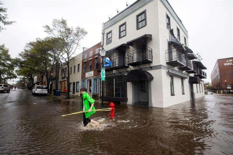 Fotografía tomada el pasado 14 de septiembre en la que se registró a varios afectados, al caminar por una calle inundada en Wilmington (Carolina del Norte, EE.UU.), tras el paso del huracán Florence. EFE/Archivo