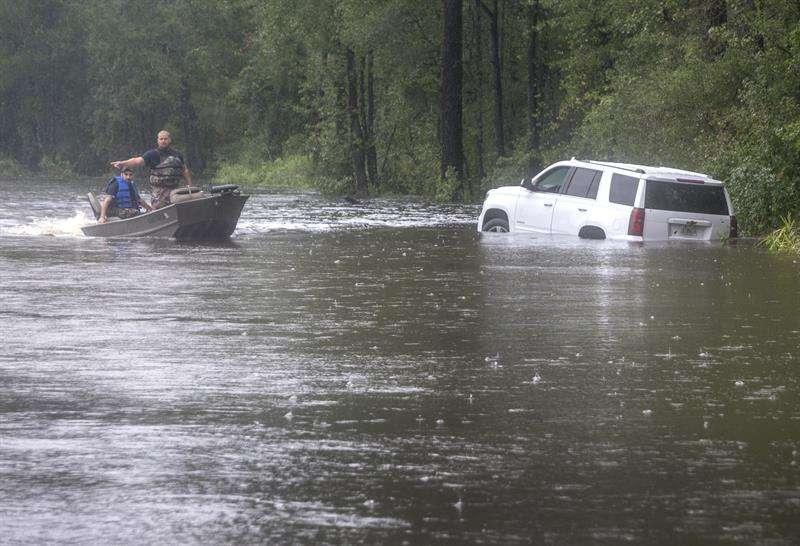 Efectivos de los cuerpos de rescate navegan en una pequeña lancha por una calle inundada de Latta, Carolina del Sur, EE.UU. EFE