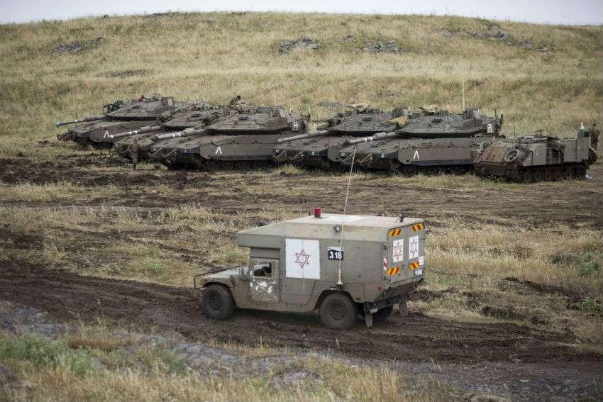 Una ambulancia militar israelí atraviesa tanques del pasado en los Altos del Golán controlados por Israel, cerca de la frontera con Siria. Foto: AP