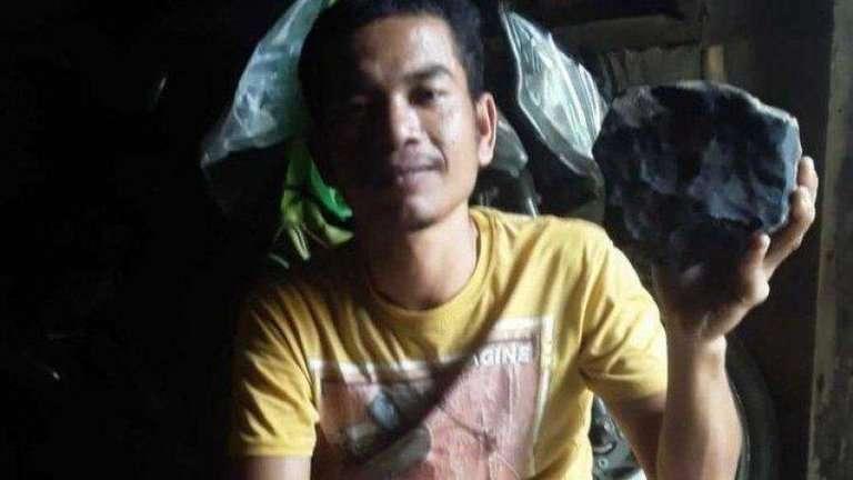 Josua Hutagalung con el meteorito que le cayó del cielo y le cambió la vida.