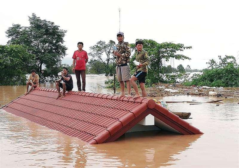 Un grupo de personas aguarda en lo alto de un tejado en una zona inundada tras el derrumbe de una presa hidroeléctrica en un pueblo cercano a la provincia de Attapeu, en Laos, este 24 de julio. EFE