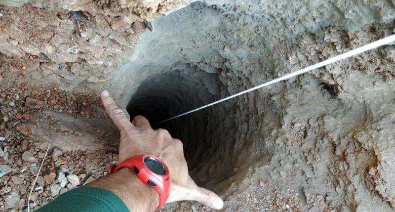 Un guardia civil señala el orificio, de apenas 30 centímetros de ancho, del pozo de más de 100 metros de profundidad por el que cayó un niño de dos años en una finca privada de la localidad malagueña de Totalán. EFE/Bomberos Málaga