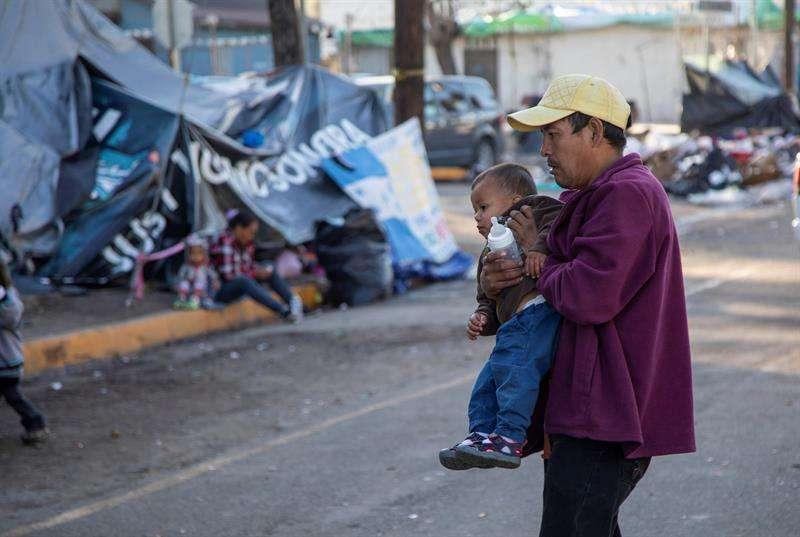 Migrantes permanecen hoy a la intemperie fuera del albergue original que resultó inhabitable luego de las fuertes lluvias en Tijuana (México). EFE