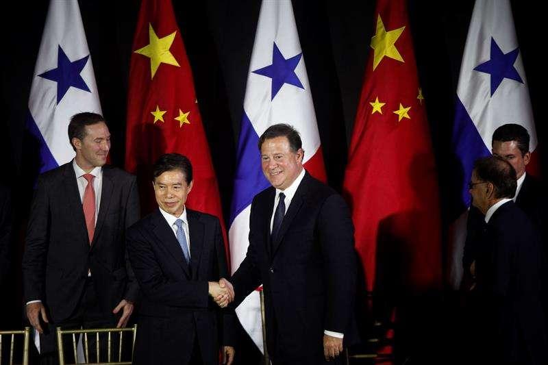 El ministro de Comercio de China, Zhong Shan (I), estrecha la mano al presidente de Panamá, Juan Carlos Varela (C), tras firmar un acuerdo de estudios de factibilidad para un sistema ferroviario y la suscripción de un TLC, el 7 de diciembre de 2017. EFE