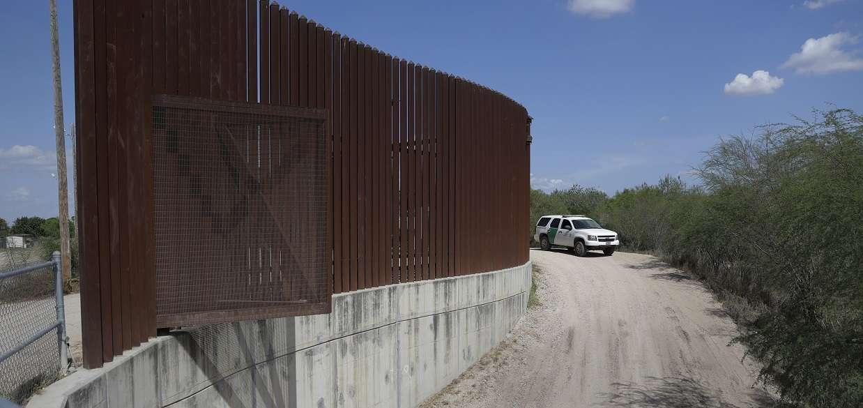 Un vehículo de la Patrulla Fronteriza y de Aduanas de EE. UU. pasa por una sección del muro del dique fronterizo en Hidalgo, Texas. AP