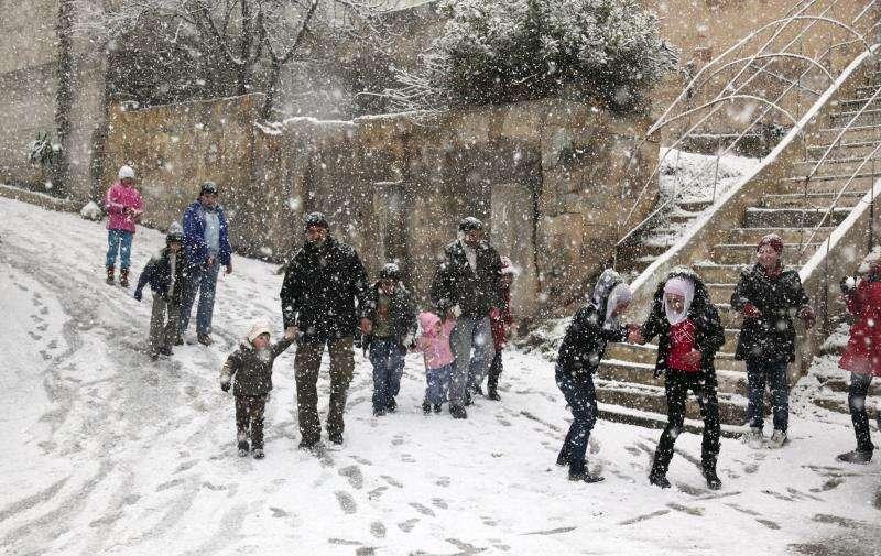 Adultos y niños caminaban bajo una intensa nevada caida hace unos años sobre Damasco. EFE/Archivo