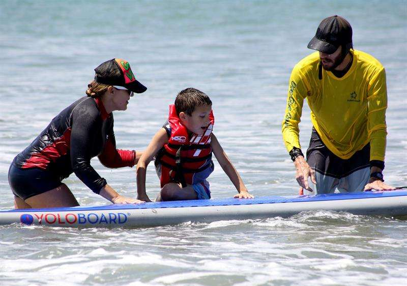 Un niño que padece autismo fue registrado al disfrutar de la brisa, las olas y la arena, durante una práctica terapéutica de surf en Ciudad de Panamá (Panamá). EFE