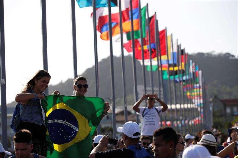 Peregrinas brasileñas se toman una fotografía frente a la bahía de Panamá, junto a las banderas de los países que participarán en la Jornada Mundial de la Juventud (JMJ) el lunes 21 de enero de 2019, en Ciudad de Panamá. EFE
