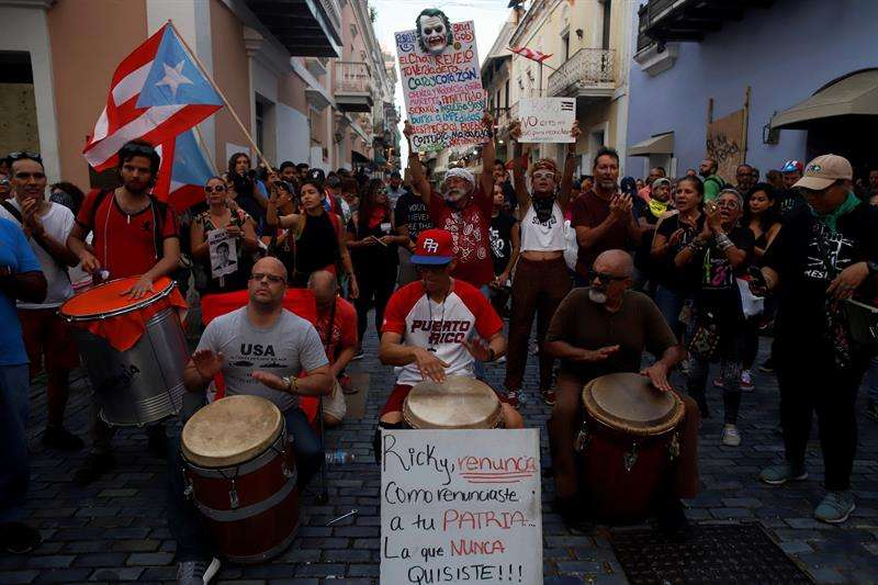 Manifestantes tocan música durante una protesta este jueves, por sexto día consecutivo, delante de la sede del Gobierno, más conocida como La Fortaleza, en San Juan (Puerto Rico). EFE