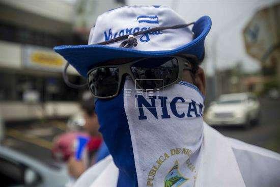 Un joven con la bandera de Nicaragua envuelta en la cara participa en un plantón frente a las instalaciones del Consejo Superior de la Empresa Privada (Cosep) en Managua (Nicaragua). EFE