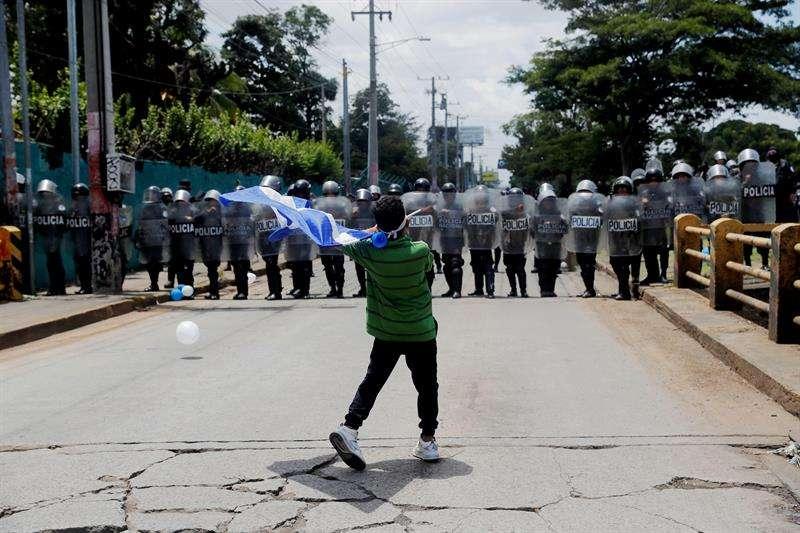 """Manifestantes que participan en la marcha """"Rescatemos la Patria"""", en contra del presidente Daniel Ortega, recriminan a los policías antimotines que bloqueen el paso hoy, domingo 16 de septiembre de 2018, en Managua (Nicaragua). EFE"""