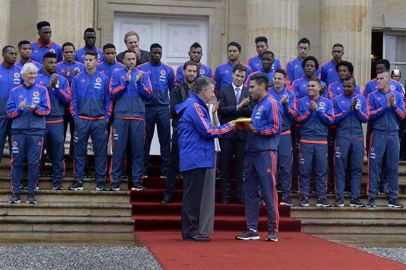 El presidente de Colombia,Juan Manuel Santos le entrega la bandera al futbolista Radamel Falcao García, junto a los jugadores de la selección colombiana de fútbol. Foto EFE